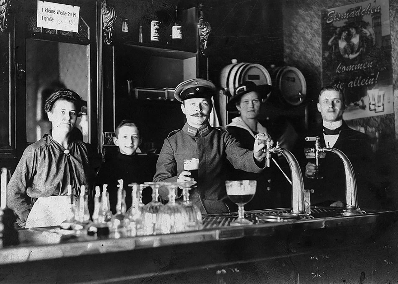 """Berliner Gaststätte, um 1916. Im Hintergrund eine """"Eismädchen"""" Werbung."""